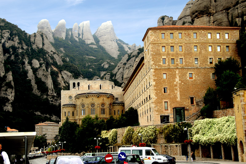 You approach the monastery and the church from the back where the parking areas are. The church faces the magnificent Montserrat mountains. On the left hand side is the apse of the Basilica. On the right and beyond the Basilica is the Monks Monastery.