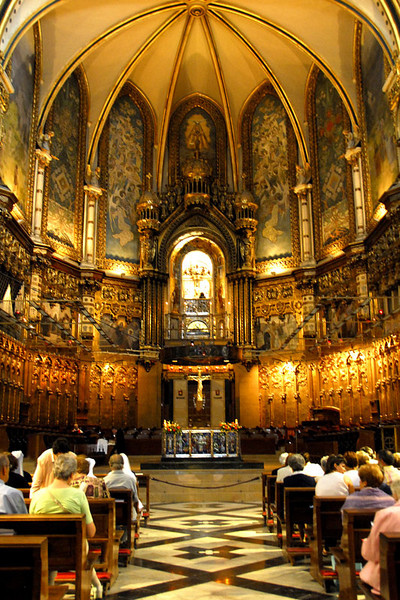 A view of the altar part. The brightly lighted arched above contains the Black Madonna. People who wants to get a closer look at the Black Madonna may go through a hall way on the right hand side, climb a stairway behind the altar walls and on the top on the level of the lighted arch. On the photo you can see a veiled person by the front of the Madonna.