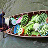 A lone boatman carrying fresh vegetables on the way to the floating market.
