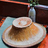 A vendor's cap and a flower vase in the boat.