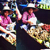 A charming woman vendor selling fresh fruits at the floating market.