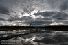 Reflections of storm clouds moving over a prairie pond