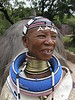 "NDEBELLE ""live-in"" royal village : This Ndebelle village is about an hour drive from Pretoria.For those not acquainted with the trick it's not he neck that gets longer, it's the shoulders that are pushed down.The couple inside the hut is actually the real Ndebelle King with his wife and his youngest son. They live in this village and show it as a working business to visitors. What a job to be on show everyday of your life always prim and proper. Not easy I tell you. They make some small dance show and simulated wedding venue (the preparation of the bride with a long beaded banner down the from the back of her head) I adore the wall paintings and the village that shows the evolution throughout centuries of the size of the hut and entrance. I can wait for the 1st mansion with sliding doors and windows. I could be mine. I would not mind living in a house painted with happy geometric colors. I will spare myself of the dung and water floor finishes althought I think the same patterns could serve as inspiration to carpets and wallpapers etc..""Esther Mahlangu"" is a woman who is not short sighted and her painted BMW won worldwide attention and her related works were and are still exhibited worldwide. She proudly displays many news paper clippings and poster relating to her work in her shop in her house. She helped develop the Ndebelle recognition and development as a well respected Art in South Africa. To visitors eyes I think the most widely known and recognized. I am the proud keeper of one of her hand painted Ostrich eggs. See more of her work at http://www.vgallery.co.za/estherpress/39.asp Here she is painting the newest Fiat 500 Can`t wait to see it finished http://www.omniauto.it/awpImages/photogallery/2008/7544/photos/fiat-500-why-africa-by-esther-mahlangu_1.jpg She is of a friendly welcoming nature and well respected more details about her life are there to be found http://www.thepresidency.gov.za/orders_list.asp?show=329 . If you come across this page. Esther, Thank you for the lovely afternoon spent in your company! Your egg is still safe and sound displayed in our house here in Canada."