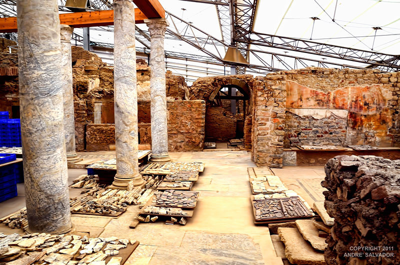 "THE PRISTYLE COURTYARD IS ON THE LEFT HAND SIDE. ON THE FLOOR LIES PIECES OF THE ""JIGSAW"" PUZZLE THAT THE ARCHEOLOGIST AND WORKERS MUST PUT TOGETHER."