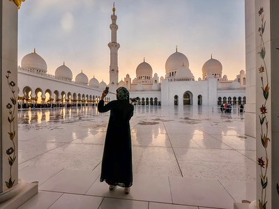 A young Muslim woman wearing a black abaya takes a selfie at a very beautiful mosque at sunset in Abu Dhabi, UAE.