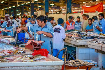 Uniformed workers preparing to sell the daily catch in the busy fresh fish section of the Waterfront Market.
