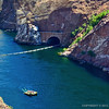 The view looking down at the Colorado River from the bus stop off the west end of the Hoover Dam Bridge. One rubber raft is seen here leaving. The two rubber rafts we will use are shown waiting in the shade beside the canyon wall.