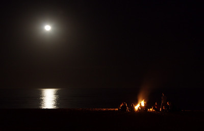 Strangers campfire on the moonlit beach.