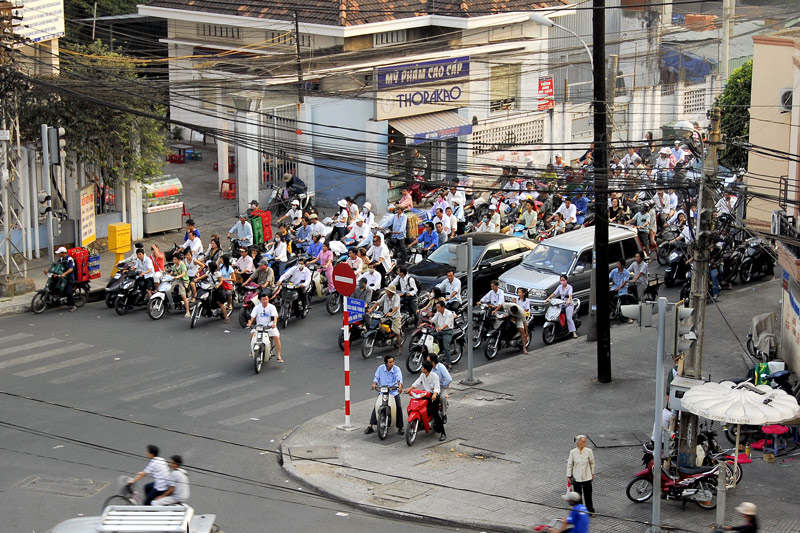 A typical street scene where the motor bikes outnumber the cars and trucks. They follow the traffic signals but if there is none, then cross the streets at your own risk.