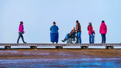The diversity of Yellowstone tourists on a boardwalk  beside a very steamy Grand Prismatic Spring.