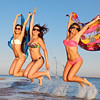 Group of girls jumping on the beach
