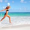 Happy woman running on the beach.