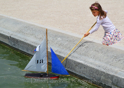 Paris is children playing with toy sailboats at Luxenbourg Gardens.