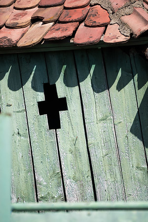 Green Plank Wall with Cross Pattern and Red Shingle Roof
