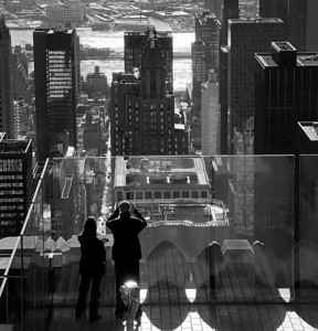 A couple of sightseers look out from the 69th floor viewing gallery (almost) at 'The Top of the Rock' across towards the East River