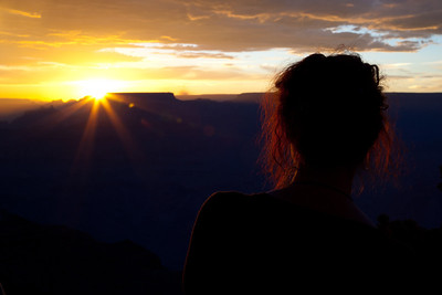 A visitor admires nature's beauty as the sun sets over the Grand Canyon.