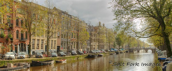 Amsterdam, The Netherlands - After a morning of overcast skies, the sun comes out along one of Amsterdam's famous canals.