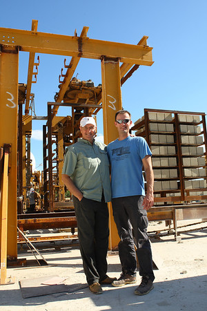 Flip and Matthew pose in front of the automated block handling system.