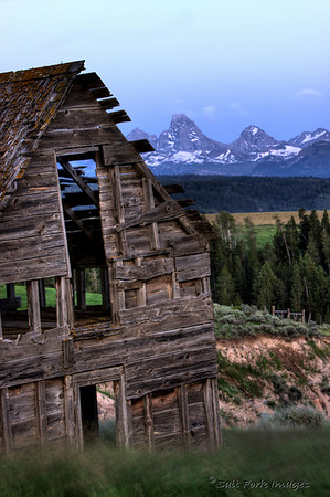 The old barn sits up on a ridge overlooking Bitch Creek with the Teton Range in the background.