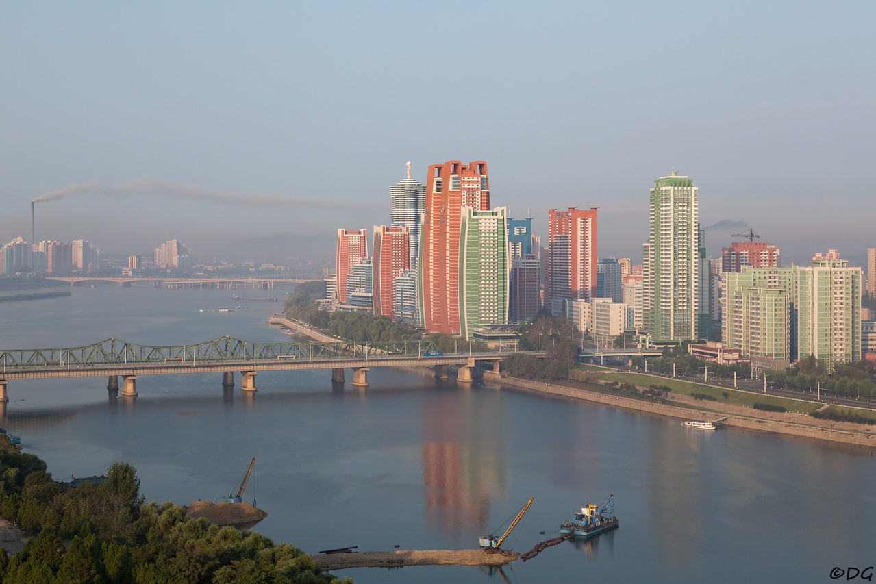 North Korea, Pyongyang. Early morning view from Yanggakdo Hotel to the southwest. Behind Yanggak Bridge the new high rise apartments on Mirae Scientists Street. Dredging for building materials in Taedong River in the foreground. In the distance; East Pyongyang Thermal Power Plant.