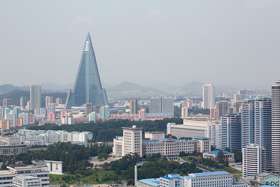 North Korea, Pyongyang. The huge but empty Ryugyong Hotel is dominating the skyline. Changjon Street apartment complexes to the right of a children's palace.