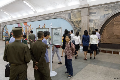 North Korea, Pyongyang. Commuters on Puhung Station reading the newspaper.