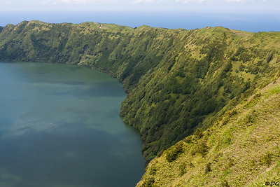 Portugal, Azores, São Miguel: Lagoa Azul in Sete Cidades and the ocean behind the crater wall.