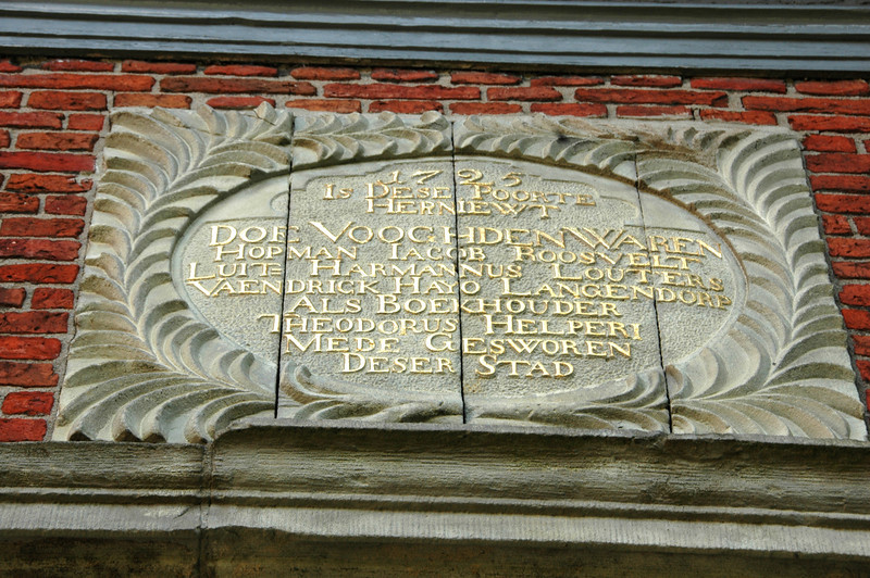 Sign above a gateway with some names of important people. Last name added in 1725.