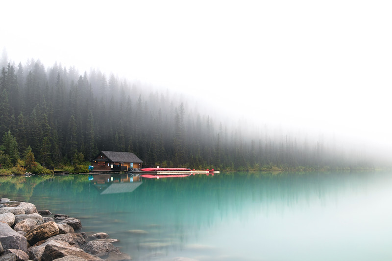 Cabin and Canoes in the Mist on the Shores of Lake Louise in Alberta, Canada
