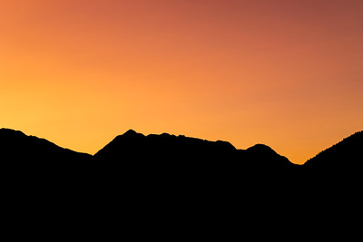 Silhouetted Mountains Against a Vibrant Sunset Sky in Canada
