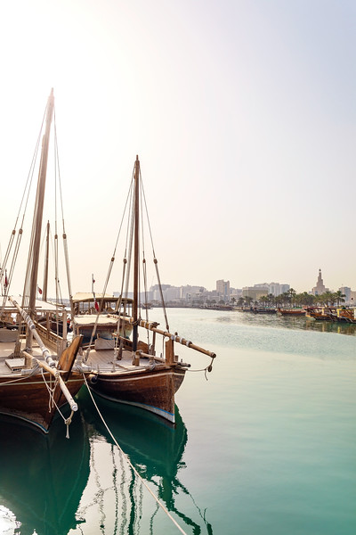 Traditional Dhow Sailing Vessels in Dock with the City of Doha Behind