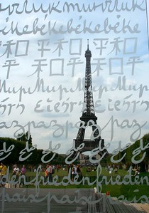 The Peace Wall behind the Eiffel Tower The monumental sculpture 'Peace Wall', designed by Clara Halter and architect Jean-Michel Wilmotte, has been placed for three months behind the Eiffel Tower at the Champ de Mars. The transparent Wall is made of two glass panels on which the word 'peace' are engraved in thirty-two languages and thirteen alphabets, of a huge esplanade made of exotic wood, and of inox pillars spelling out infinitely the same word. Loosely inspired by the Wailing Wall in Jerusalem, each visitor has the possibility to leave a message in the wall cracks built in intentionally.