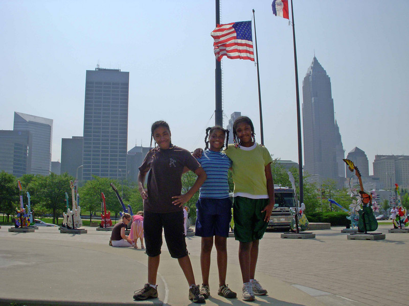 Standing in front of Rock Hall with a bit of the city's skyline behind them.