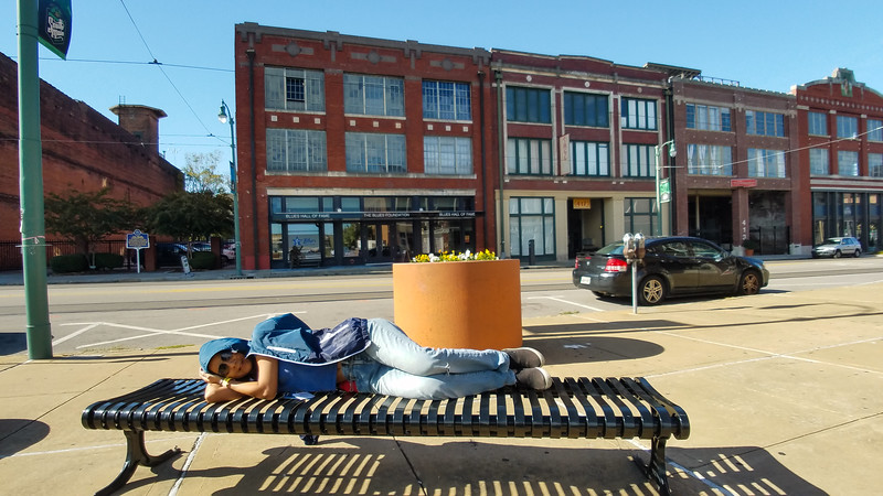 Tourist sleeping in front of the Blues Hall of Fame in Memphis, Tennessee.