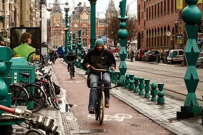 Amsterdam - Damrak street bike rider on the cold