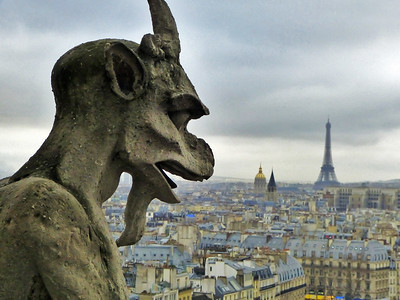gargoyle monster watching the roof tops of Paris and the Eiffel Tower