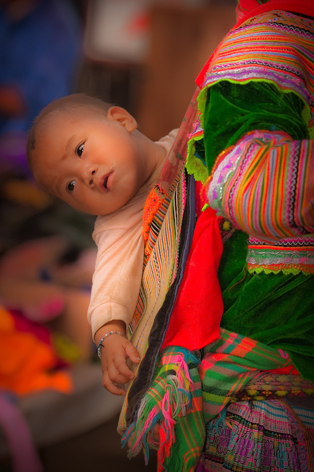 baby on moms back at the Sunday market in Sapa Vietnam.