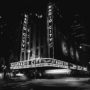 Radio City Music Hall at night with the blur of cab traffic.
