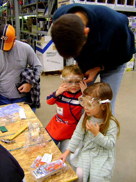 GOGGLE UP!<br /> Lowe's is concerned enough about the safety of the kids that they insist they wear safety goggles when working on the projects. Bill makes a final adjustment on Jack's.
