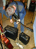 SEAN TUNES UP<br /> Sean tunes up his beautiful black guitar, while my humble acoustic one looks on from the guitar stand. Don't worry, buddy -- I still love you.
