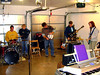 THE GARAGE BAND<br /> One of the things I got to do while I was here is sit in with their garage band on acoustic guitar. My guitar wasn't amplified, which was probably a good thing, but it was fun, anyway. I eventually got to play Sean's black electric guitar for a song or two, while he wailed away on harmonica and vocals. I've got to get me one of those someday.<br /> <br /> L to R: Steve (drums, percussion), Mary (keyboard, vocals), Scooter (stage manager; behind folding chair), Wayne (electric bass), Sean (electric guitar, harmonica, vocals), and Laura (electric guitar)