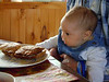 MMM . . . FOOD!!!<br /> Ruth Jean doesn't quite know what to think of what's on that plate, but she sure looks like she wouldn't mind a sample. She hasn't gotten to the everything-into-the-mouth stage yet, but when she does, I wouldn't hold her quite so close to my lunch.