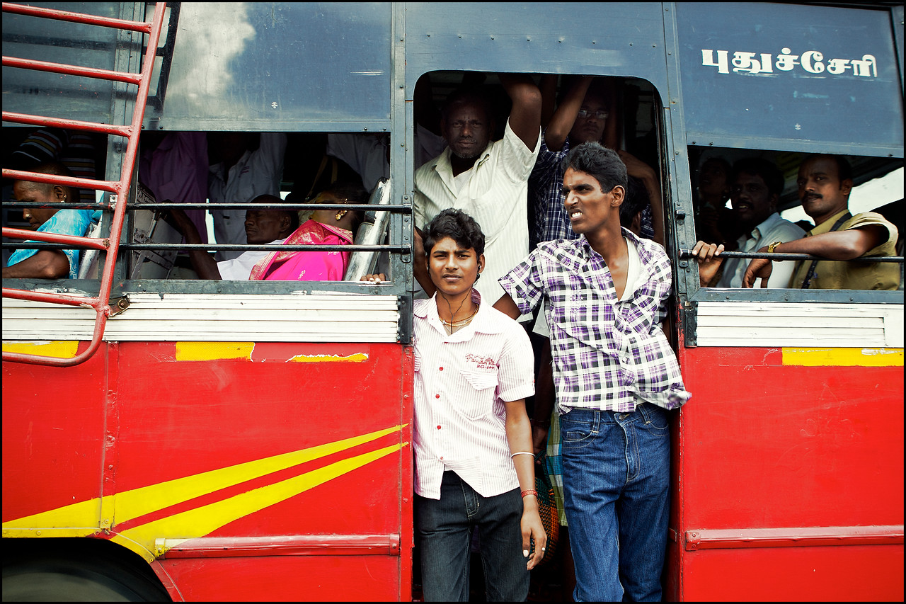 Crowded busses are a common public transportation scene.<br /> (India)