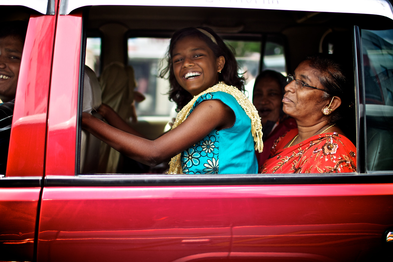 A beautiful young girl flashes a smile during stop and go traffic.<br /> (India)