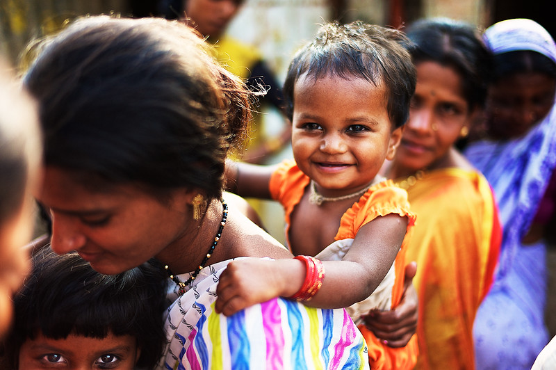 A young Indian girl smiles as she plays behind her mother.