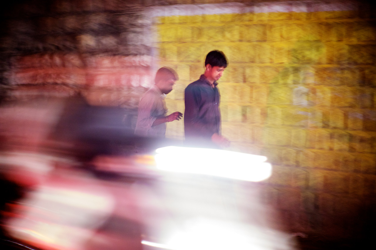 In a whirl...<br /> 2 pedestrians in the middle of nighttime traffic.<br /> (India)