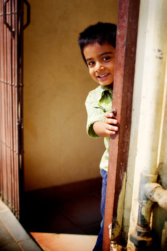 A shy child tries to hide from the camera.<br /> (India)