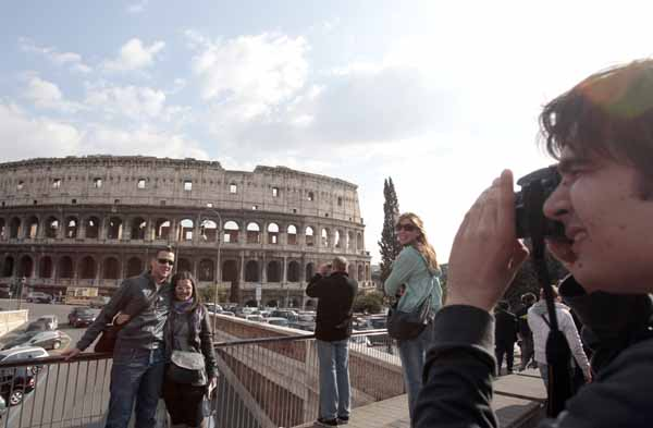 This Tuesday, March 22, 2011 photo shows tourists as they take pictures in front of Rome's ancient Colosseum. The Vatican travel agency for pilgrimages said prices on rooms might tumble in the coming weeks because predictions of upward of 1 million people pouring into the city for Pope John Paul II's beatification ceremony could scare off potential hotel guests.    (AP Photo/Gregorio Borgia)