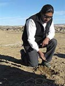 In this photo taken Jan. 23, 2011, Hopi anthropologist Micah Loma'omvaya picks up a hand of dirt during an agriculture tour on the Hopi reservation in northern Arizona.  The tours have fed the desire of visitors to learn about one of the oldest indigenous tribes in America but also an economic need where business opportunities are scarce. (AP Photo/Felicia Fonseca)
