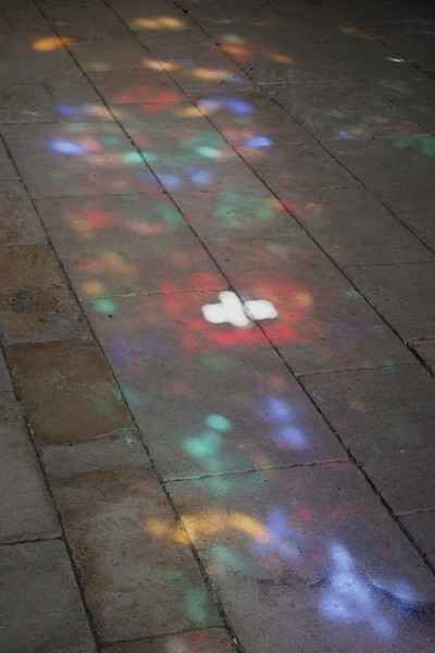 Reflections on the floor from a stained-glass window.